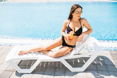 Young woman in swimsuit relaxing with cocktail near pool. Summer time Royalty Free Stock Photo
