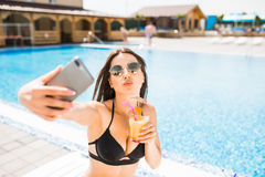 Young woman in swimsuit relaxing with cocktail near pool and take selfie on phone. Summer time Stock Photo
