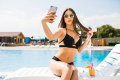 Young woman in swimsuit relaxing with cocktail near pool and take selfie on phone. Summer time Stock Image