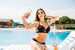 Young woman in swimsuit relaxing with cocktail near pool and take selfie on phone. Summer time Royalty Free Stock Photography