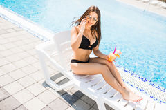 Young woman in swimsuit relaxing with cocktail near pool and tal Stock Images