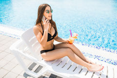 Young woman in swimsuit relaxing with cocktail near pool and tal Royalty Free Stock Photo