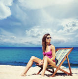 A young woman in a swimsuit relaxing on a deckchair on the beach Royalty Free Stock Photo