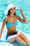 Young woman in a swimsuit relaxing near the pool Royalty Free Stock Photo