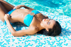 Young woman in a swimsuit relaxing near the pool Royalty Free Stock Image