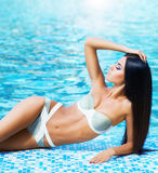Young woman in a swimsuit relaxing near the pool Royalty Free Stock Photos