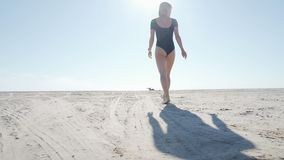 Young woman in swimsuit running on sea beach. Girl jogging along ocean shore. Female tourist having fun. Concept of stock video