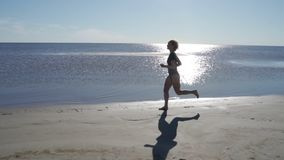 Young woman in swimsuit running on sea beach. Girl jogging along ocean shore. Female tourist having fun. Concept of stock video footage