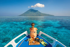 Young woman in swimsuit sit on boat with a mask and flippers loo. King to a clean sea and volcano Manado Tua. North Sulawesi, Indonesia stock photo