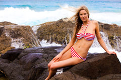 Young Woman in Swimsuit Sitting on Rocks on the Be Royalty Free Stock Photo