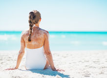 Young woman in swimsuit sitting on sandy beach . rear view Royalty Free Stock Photos