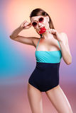 Young woman in swimsuit and sunglasses eating heart-shaped candy. Attractive young woman in swimsuit and sunglasses eating heart-shaped candy Royalty Free Stock Images