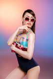 Young woman in swimsuit and sunglasses holding bottles with refreshing summer drinks and looking away Royalty Free Stock Photo