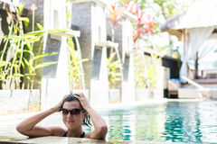 Young woman in swimsuit in swimming pool in gorgeous resort, luxury villa, tropical Bali island, Indonesia. Stock Photography
