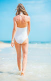 Young woman in swimsuit walking at seaside. rear view Royalty Free Stock Photo