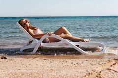 Young woman in a swimsuit wearing sunglasses lies on a deckchair stock image