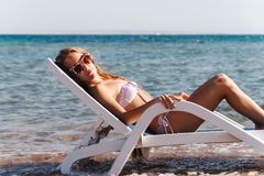 Young woman in a swimsuit wearing sunglasses lies on a deckchair royalty free stock images