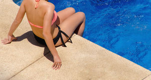 Young woman in swimwear sitting on the poolside Stock Photo