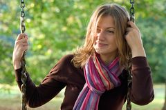 Young woman on a swing. A young woman wearing colourful scarf sitting on a swing in a park Royalty Free Stock Image