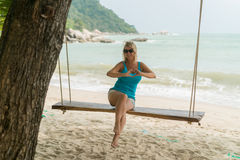 Young woman on swing on a beach Stock Images