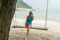 Young woman on swing on a beach Stock Photography