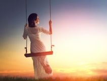 Young woman on a swing. Beautiful young woman on a swing on summer sunset outdoors Royalty Free Stock Image