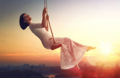 Young woman on a swing. Beautiful young woman on a swing on summer sunset outdoors Royalty Free Stock Photography