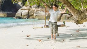 Young woman on a swing on the coast of tropical sea stock video footage