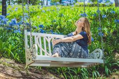 Young woman on a swing in a flower garden Royalty Free Stock Images