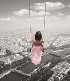 Young woman on a swing on the Paris town backround Stock Photo