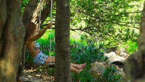 Young woman on swing in tropical forest on river shore. Beautiful woman swinging on swing in jungle forest. Wild nature. Background stock video footage