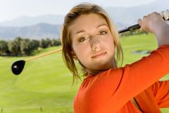 Young Woman Swinging Golf Club stock photography