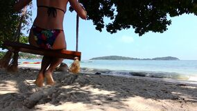 Young woman is swinging on swings at the seashore