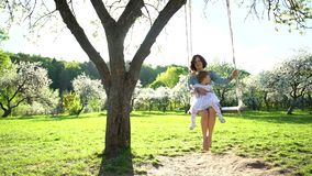 Young woman swinging on wooden swing with little pretty girl in dress. Static stock footage