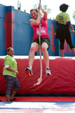 Young Woman Swings With Rope In Crazy Obstacle Race Stock Images