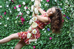 Young woman swings on swing overgrown with flowers. Next to green hedge Royalty Free Stock Photo