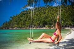 Young woman swings on a tropical beach Stock Photography