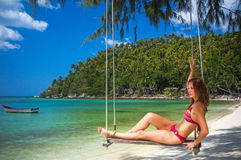 Young woman swings on a tropical beach Stock Photo