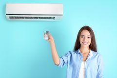 Young woman switching on air conditione. R against color background Royalty Free Stock Photos