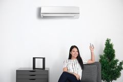 Young woman switching on air conditioner. While sitting in armchair at home Stock Image