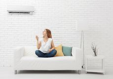 Young woman switching on air conditioner. While sitting on sofa at home Royalty Free Stock Photos