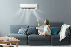 Young woman switching on air conditioner. While sitting on sofa at home royalty free stock photography