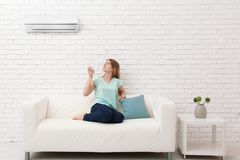 Young woman switching on air conditioner. While sitting on sofa at home Royalty Free Stock Photo