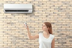Young woman switching on air conditioner. Against brick wall background Royalty Free Stock Images