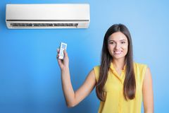 Young woman switching on air conditioner. Against color background Stock Photos