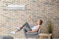 Young woman switching on air conditioner. While sitting in armchair at home Royalty Free Stock Image