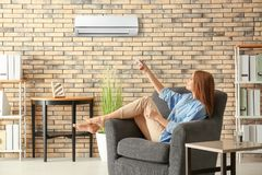 Young woman switching on air conditioner. While sitting in armchair at home royalty free stock photography