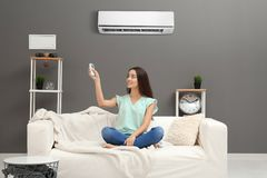 Young woman switching on air conditioner. While sitting on sofa at home stock image