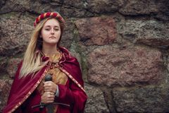 Young woman with sword in hand on stone wall background .with copy space.  royalty free stock photography