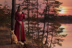 Young woman with a sword. A young woman in medieval clothes with a sword stands beside the river, with a Fox against the setting sun royalty free stock images